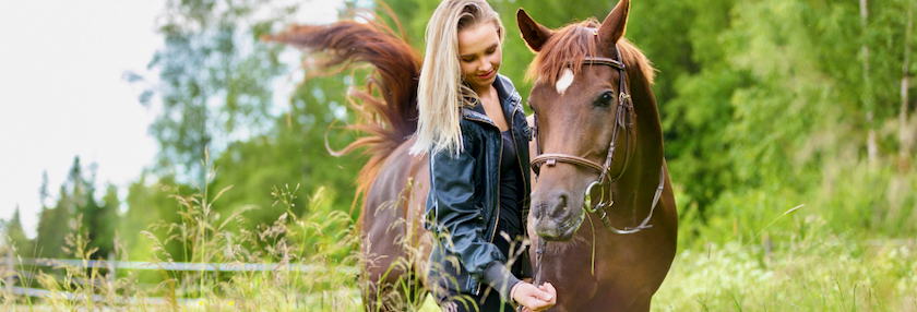 Woman offering all natural treat to horse