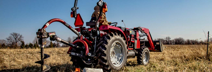 Massey Ferguson tractor with posthole attachment